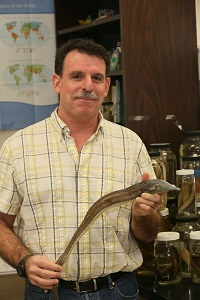 Man in plaid shirt holding a snake